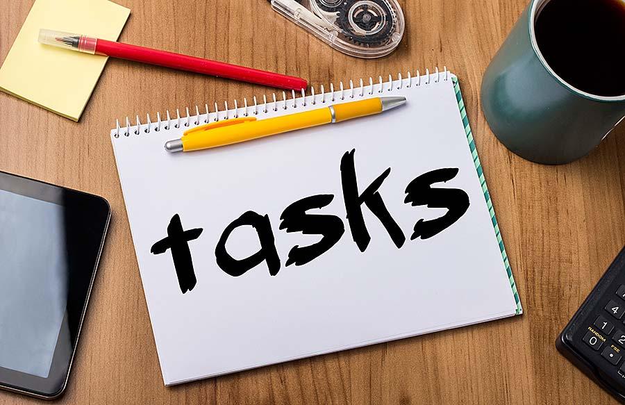 """Schriftzug """"tasks"""" auf einem Block mit Stiften auf einem Schreibtisch"""