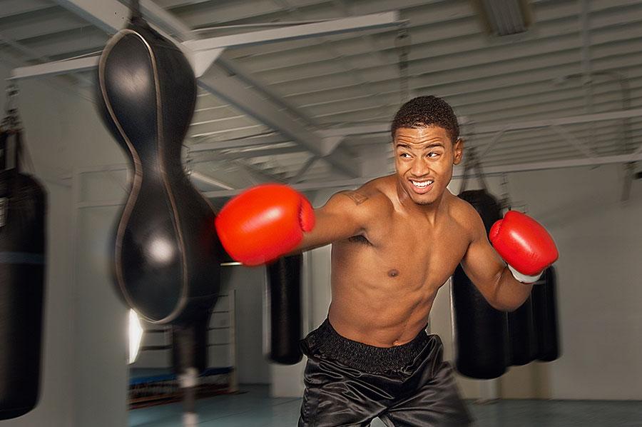 Boxer mit roten Boxhandschuhen, der an einem Sandsack trainiert