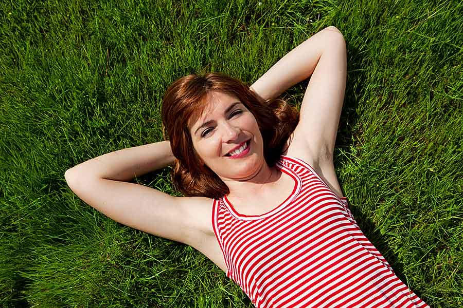 Frau mit verschränkten Armen, die entspannt im Gras liegt
