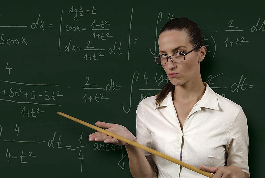 Strenge Lehrerin mit Zeigestock vor einer Tafel mit Formeln