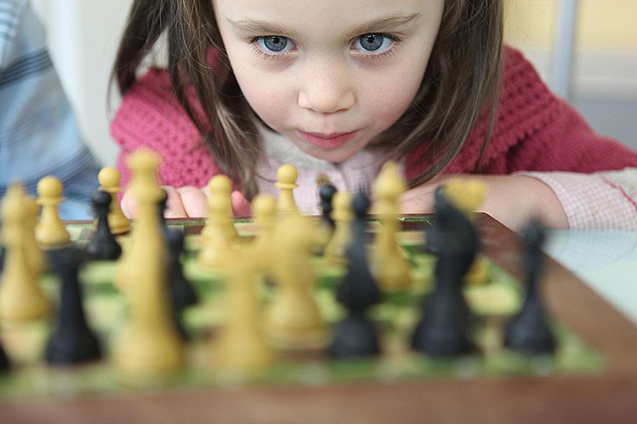 Kleines Mädchen schaut konzentriert auf ein Schachspiel