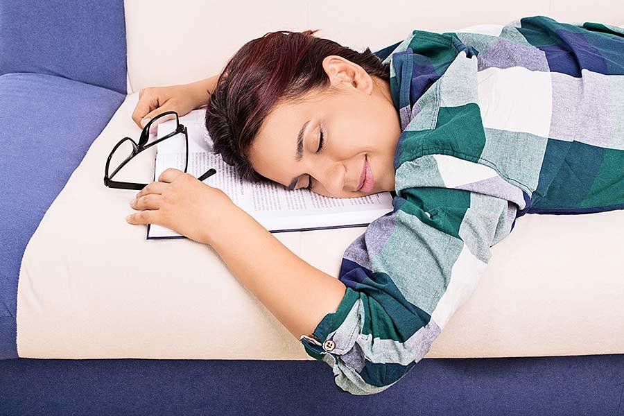 Junge Frau schlafend auf einem Sofa mit einem Buch und einer Lesebrille