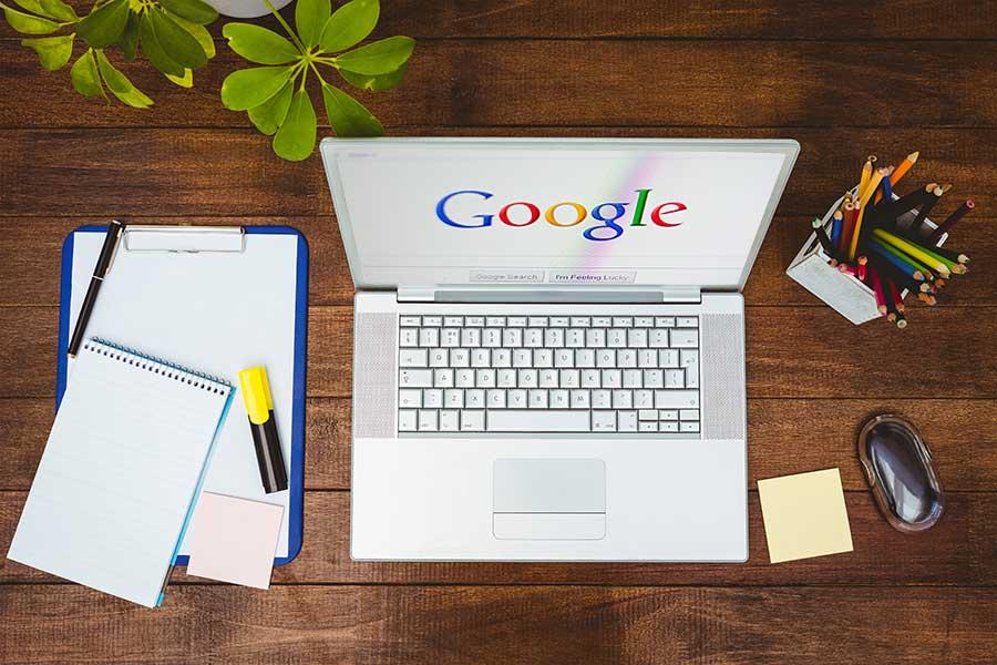 Laptop von oben mit Bild Suchmaschine Google und Utensilien darum herum