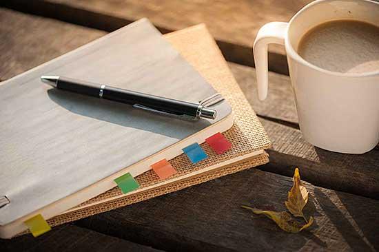 Kaffeetasse und Notizbuch auf einem alten Holztisch im Abendlicht