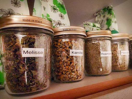 Aufbewahrungsgläser mit verschiedenen Teesorten aufgereiht in einem Regal