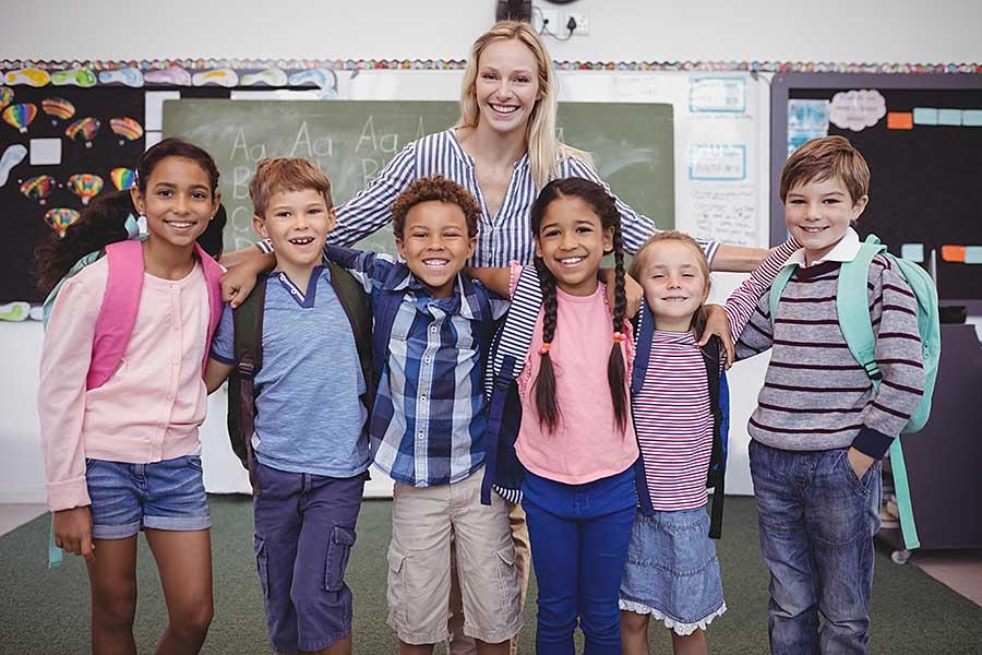Glückliche Lehrerin mit ihren Schülerinnen und Schülern in einem Klassenzimmer vor einer Tafel