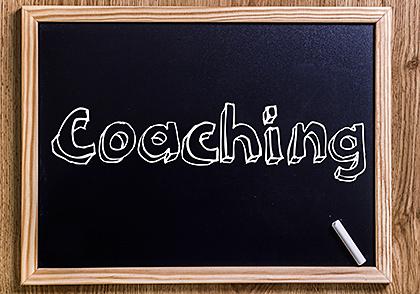 Schriftzug Coaching auf einer schwarzen Handtafel