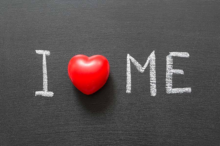 Rotes Herz mit Schriftzug I (love) me auf einer Schiefertafel